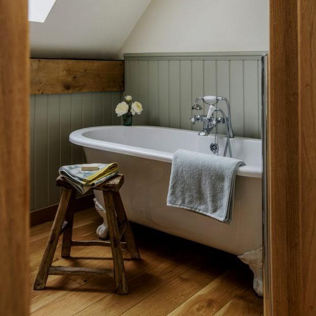 Phòng tắm nhỏ gọn với bồn tắm có chân đế độc lập và tấm ốp gỗ xanh